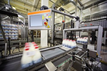 Conveyor with wrapped milk bottles at big factory